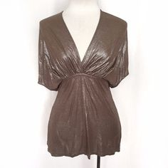 """Stella McCartney Metallic Flecked Top Shimmering brown metallic flecked top with a self-tie belt at the empire waistline. Short batwing style sleeves with a v-neck and ruched panels above the bust. 75% rayon; 25% flax. Dry clean. Size/care tag is missing but this fits like an Italian size 40 (US 2-4 or XS-S). Bust: approximately 18""""-20"""" flat across. Waist: 16"""" flat across. Length: 27"""". Besides having no care tag it is in EUC. Gold model in last pic is a different color from what I'm selling…"""