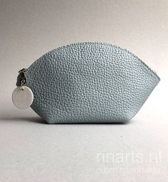 WEDGE: A very versatile zipper pouch.  This pouch is for any occasion: you will never leave home without it! You can use it as a a bag-organizer, cosmetic bag, make-up bag, phone case or use it as a purse.  The design makes the bag very spacious, yet compact.  This WEDGE pouch: - is made of light ice blue (almost light gray) full grain cow leather; the leather is thick and medium firm. - has a white and silver metal zipper - ice blue and white circle zipper pull - is not lined.  Please note…