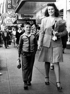 With a cacophony of marquees and merchant come-ons behind them, West Seattleite Virginia Slate (right), 22, and nephew Jerry Johnson, 8, are caught by a candid street photographer strolling north along the west sidewalk of Seattle's Fourth Avenue between Pike and Pine streets in mid-1945. (Courtesy Clay Eals)