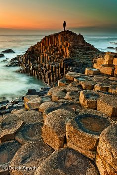 Northern Ireland: A solitary figure stands alone at the Giants Causeway watching…