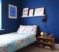 Bold, colourful kid's room. IKEA HEKTAR clamp lamp as bedside light. Apple crate as bedside table. Walls painted in Little Greene Deep Space Blue.