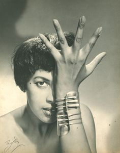 """A model wears Art Smith's """"Modern Cuff"""" Bracelet, circa 1948. Art Smith (1917-1982) was a modernist jeweler born in Cuba to Jamaican parents who eventually emigrated to Brooklyn. He opened his first shop on Cornelia Street in Greenwich Village in 1946 - no small feat. Along with being covered by magazines like Vogue and Harper's Bazaar, Smith, an avid jazz lover, once made cufflinks for Duke Ellington which included some notes from Mr. Ellington's """"Mood Indigo."""""""
