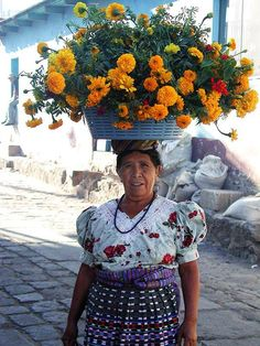 Flowerseller, San Pedro la Laguna, Solola, Guatemala   MIAMI STREET VENDOR   by Sylvia Mzz     The street vendor has a bucket full of beauty roses in colors God never intended I always buy orange ones or sunflowers to go with my walls he always gives me extras strays from damaged bouquets   He smiles because he knows they are more than just decorations to me   I love him like a brother with his round face, tanned skin and neat polo shirt because he smiles through the stifling heat   Because…