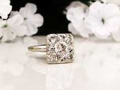 This bright, sparkling vintage engagement ring, circa late Art Deco, is a square shaped illusion mount of one larger solitaire with four
