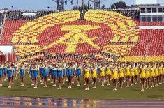In überdimensionaler Größe wird am 30.07.1987 das aus Hammer, Zirkel und Ehrenkranz bestehende Staatssymbol der DDR von Tausenden Teilnehmern des VIII. Turn- und Sportfestes auf den Rängen des Leipziger Zentralstadions gebildet. Im Vordergrund gelb und blau gekleidete Turnerinnen bei ihrer Vorführung.   Rechte: dpa