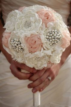 """Unique, hand sewn, fabric bridal bouquet with ivory and pink flowers and an ivory ribbon wrapped handle. Rhinestone and pearl embellishments are included. This bouquet measures approximately 13"""" tall"""