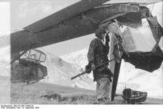 A German glider trooper next to a DFS 230 C-1 glider damaged during landing, Gran Sasso, Italy, 12 Sep 1943
