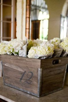 Newsprint-Wrapped Hydrangea: Vintage newsprint-wrapped hydrangea were tied with jute strings and nestled into numbered crates from Gabby. Inspired by old-school newsstands when flowers were often sold wrapped in newsprint, the floral displays served a dual purpose: party decoration and postparty favors for guests.