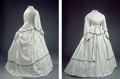 Kjole af hvid bomuld med påtrykt blomstermønster. Kjolen består af et liv, et skørt, et skød og et overskørt med tunikaeffekt