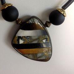 Collier pendentif triangulaire dégradé de doré, noir, blanc; gris.