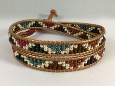 Reflection - double wrap bracelet is made of hand woven Japanese seed beads in shades of purple, teal, rose pink, oxblood brown and platinum gold colored metallic beads. All hand woven on high quality metallic copper colored leather cord and finished with an antique bronze colored