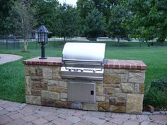 Outdoor kitchen constructed with limestone and a brick countertop. #TopekaLandscape