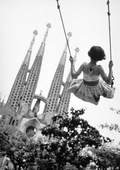 the sagrada familia (young girl on swing in playground with the towers of the…