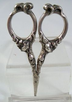 ornate American Sterling Embroidery Scissors. The marked sterling scissors has a floral design with flowers on the bottom of the bows and a plume like design on the top