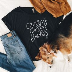 Designed by OlivePaperCo Perfect loos and comfortable top to add to your wardrobe! Details Bring out your crazy corgi lady in this super cute dolman shirt! Content + Care - Heather Black Tri-Blend Dolman T-shirt - White Lettering - Pre-shrunk cotton, polyester, rayon tri-blend - Machine wash - Hang to dry - Made in the USA