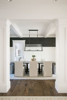 A rectangular glass pendant hangs over a salvaged wood dining table surrounded by natural linen dining chairs placed on a cream colored rug. Dining Room Colors, Dining Room Walls, Dining Room Design, Grasscloth Dining Room, Linen Dining Chairs, Dining Tables, Dining Room Inspiration, Design Furniture, Bar Stool