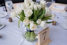 White Tulip Centerpieces and Wooden Table Numbers Tulip Centerpieces Wedding, Wooden Centerpieces, Tulip Wedding, White Centerpiece, Elegant Centerpieces, Wedding Ceremony Decorations, Table Decorations, Wedding Flowers, Wooden Table Numbers