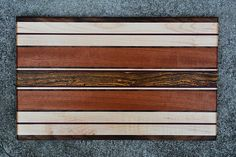 This cutting board is made out of five different species of wood. The majority of the board is Tigerwood and Bocote with Purpleheart, Curly Maple, and Black Walnut accents. Each board is sanded and finished to leave a completely smooth surface. The edges of the board are rounded