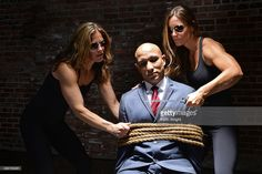 Man in suit tied up with rope and held hostage by two strong women.
