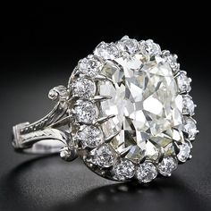 We had one of our finest jewelers expertly recreate the mounting (which was worn-out beyond salvation) for this scintillating and sizzling carat antique cushion-cut diamond which exhibits a warm light yellow hue. At arms length, the already spready d