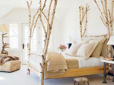 originelles Schlafzimmer mit Birkenstämmen als Beinen des Betts