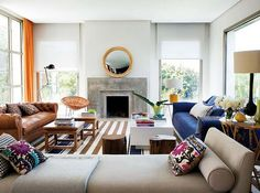 Mismatched couches. Striped rug. Round mirror. Cool chair. Chaise. Rad pillows.