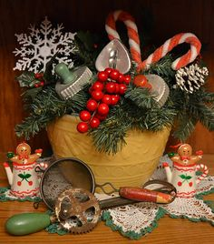 """""""My yellow bowl filled with greenery and my grandmother's old egg beater and sifter. I can only imagine the cakes she mixed with these old utensils.   Little gingerbread people popping out of cherry embellished teapots.  They are actually ornaments."""""""