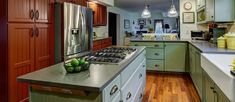 This East Greenwich RI farmhouse styled kitchen remodel used granite, painted shaker cabinets, recessed pendant lighting and a ceramic backsplash.