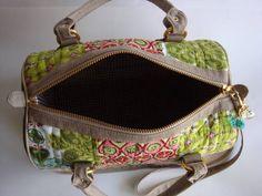 Bolsa feita de patchwork e com laterais de lona estonada. Possui alça de mão e transversal