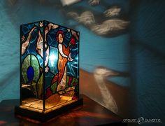 Lampe en vitrail réalisée avec du verre soufflé. Lampe composée de 5 panneaux. Chaque pièce de verre est peinte à la grisaille et cuite à 630°C. Le socle est en chêne.
