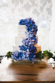 A cascade of blue hydrangeas adds a pretty pop of color to this nearly naked wedding cake | Image by BAKEPHOTOGRAPHY