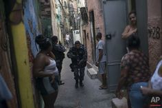 """In this June 29, 2016 photo, a police officer patrols among residents during an operation against drug traffickers at the """"pacified"""" Jacarezinho slum in Rio de Janeiro. The Pacification Police Units, known by the Portuguese acronym UPP, were created in 2008, setting up community stations in at-risk areas, mostly near sports venues, posh tourist districts and downtown. A drug gang leader called the program a """"facade."""" He said that drug dealers were initially worried and kept a low profile…"""
