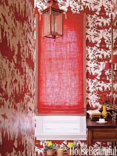 Lively scenes and vivid wallpaper reds, plus an eye-catching crimson shade, distract attention from the awkward space designer Meg Braff had to work with.   - HouseBeautiful.com