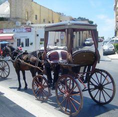 Il- Karozzin  (horse drawn carriage in Malta) taking tourists around the city