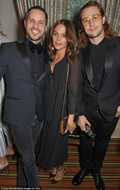Classic: For her evening out, the beauty was styled in a pleated, tea-length sheer black dress. She is seen withCDLP co-founders Andreas Palm (L) and Christian Larson