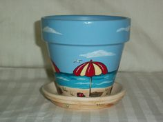 This is a cute little terracotta flower pot hand painted by me in a tropical beach theme. You can almost imagine yourself sitting under that