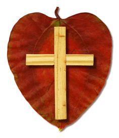 A heart shaped leaf with a Christian cross.