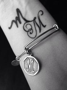 Charmed arm. M&M tattoo. (Personally hand written -please use as inspiration only). Alex and Ani M charm. Wrist tattoo.  #charmedarms #alexandani