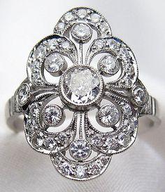 Circa 1930s. This elegant platinum Art Deco diamond ring features a central bezel-set, old European-cut diamond. Online at Isadoras.com.