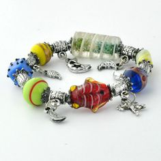 An elasticated bracelet featuring numerous multi-colored glass ornaments bearing the Evil Eye symbol. Handcrafted in Izmir, Turkey.