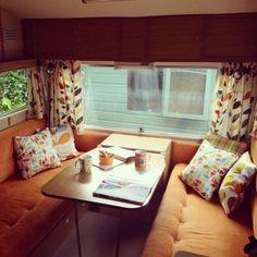 camping car aménagement canapé orange coussins à motifs rideaux