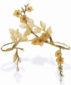 AN ART NOUVEAU HORN AND GOLD TIARA, BY PAUL LIENARD. Designed as carved horn leaves and apple blossoms with collet-set diamond pistils, to the textured gold branches and twigs, enhanced by baroque pearl buds, suspending two detachable clusters of flowers and leaves of similliar design, mounted in gold, circa 1900, in a Paul Liénard green fitted case.