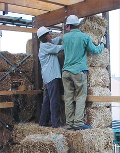 A photo of two workers installing straw bales in a timber frame.