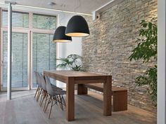 salle contemporaine avec chaises Eames et mur en pierre