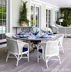 White wicker chairs surround the ceramic-topped table, which is on the porch just outside the kitchen. - Photo: Tria Giovan / Design: Kenneth Alpert