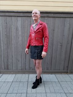 Black faux leather skirt with laces, red faux leather jacket, nude nylons, black chunk high heeled shoes.