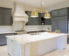Gorgeous kitchen features charcoal gray cabinets paired with white marble countertops and white marble backsplash framing plastered range hood over integrated gas cooktop.