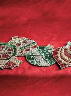 Dazzle your guests this holiday season with the sparkling Set of Four Kim Seybert Beaded Ornament Coasters that boast four unique and festive designs.