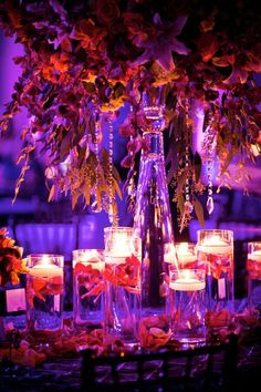 The combination of a main centerpiece with the floating candles wedding table decor is very pretty. Also, the floating candle decor would be fast and easy to replicate Floating Candles Wedding, Tall Wedding Centerpieces, Wedding Decorations, Centerpiece Ideas, Peacock Centerpieces, Purple Centerpiece, Elegant Centerpieces, Wedding Table, Wedding Reception