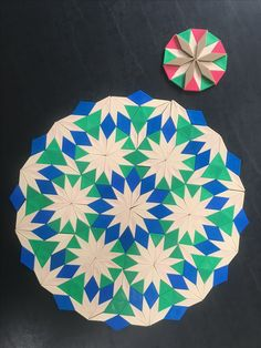 Mandala based on a fourth diamond-triangle nonperiodic tiling using pattern blocks. Each diamond's orientation in the substitution rule can be chosen so that the mandala is reflectively symmetric. (Original)